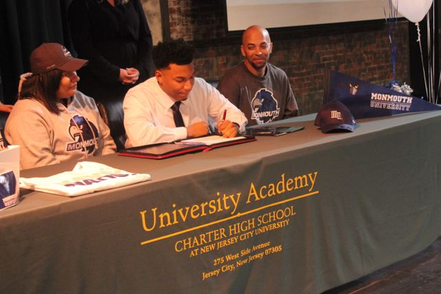 Senior+Devell+Jones+signs+his+letter+intent+with+his+parents+by+his+side.+Jones+recieved+a+full+scholarship+to+Monmouth+University.+Photo+by+Mahkiya+Gresham